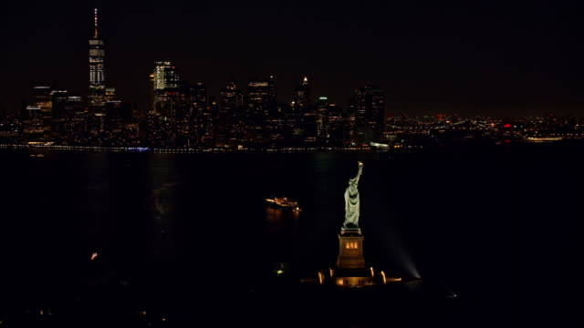 AERIAL Statue of Liberty and Manhattan at night