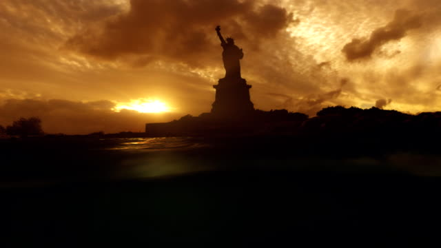 Statue Of Liberty from water level sun sets behind it. video