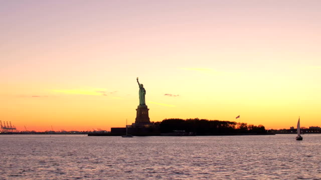 Statue of Liberty in New York Harbor against gorgeous fiery orange sunset video