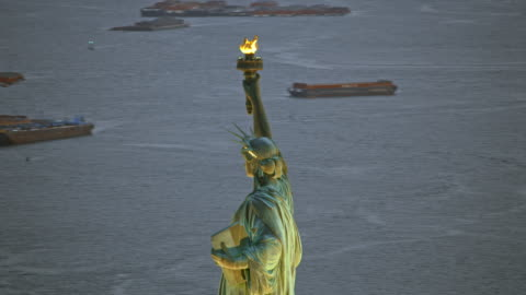 AERIAL Statue of Liberty in New York Harbor in the evening Aerial shot of the Statue of Liberty on Liberty Island in New York Harbor in the evening. Shot in NY, USA. aircraft point of view stock videos & royalty-free footage