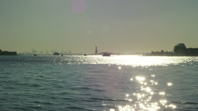 Statue of Liberty in the Harbor with a Boat at Sunset Wide Angle