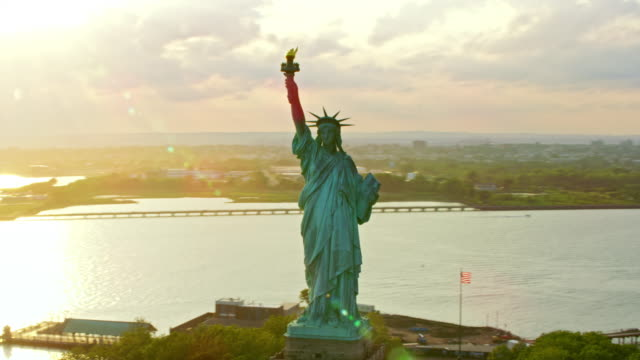 AERIAL Statue of Liberty on Liberty Island at sunset with NYC in the background