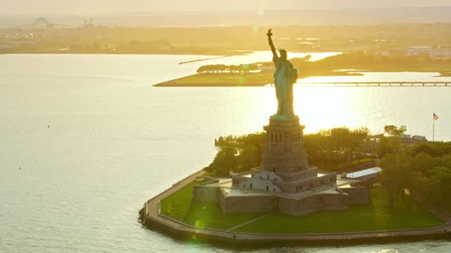 AERIAL Statue of Liberty on Liberty Island shining in setting sun