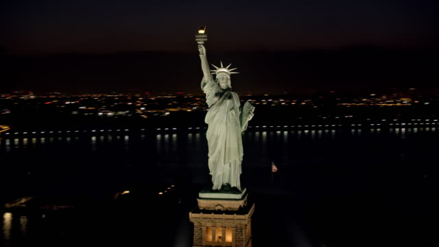 AERIAL Statue of Liberty shining in the night with Lower Manhattan seen in the background