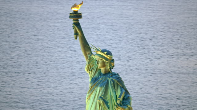 AERIAL Statue of Liberty with lit torch in the evening