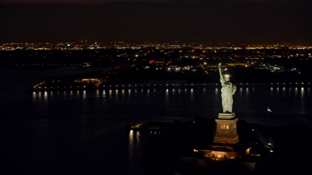 AERIAL Statue of Liberty with New York in the background at night