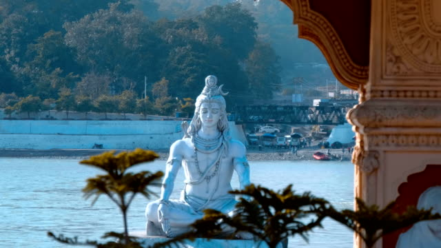 staty av shiva i rishikesh på stranden av den heliga floden ganges - india statue bildbanksvideor och videomaterial från bakom kulisserna