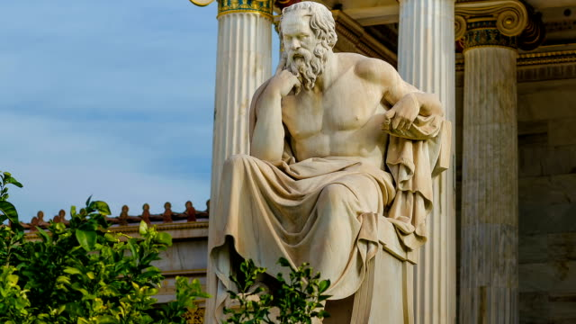 vídeos de stock e filmes b-roll de statue of the greek philosopher socrates on a marble chair, background of columns and sky. - monumento