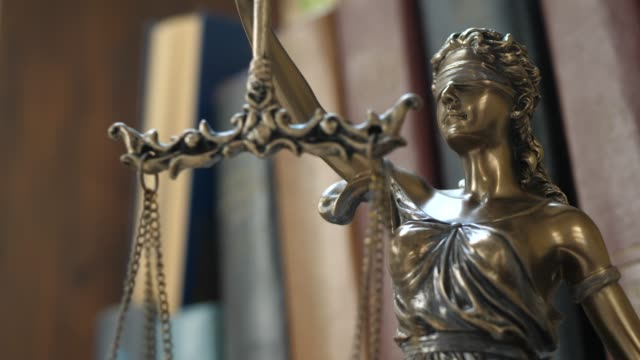 statue of themis or lady justice on books background - sistema legale video stock e b–roll