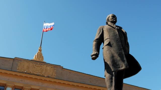 statue von vladimir lenin an russische flagge hintergrund - kommunismus stock-videos und b-roll-filmmaterial