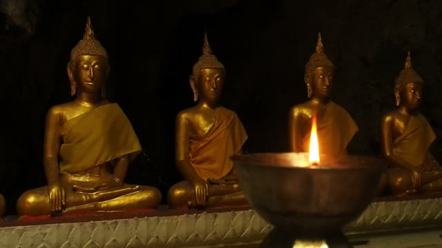 Statuette of Buddha and a burning candle video