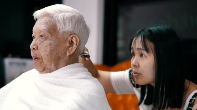 bleiben sie zu hause quarantäne: seniorin bekommt einen haarschnitt von enkelin zu hause - friseur lockdown stock-videos und b-roll-filmmaterial