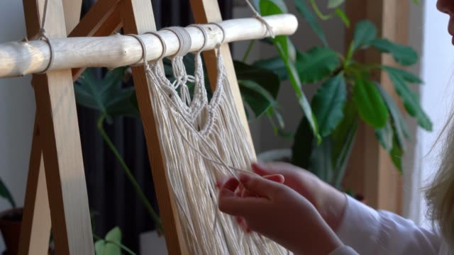stanna hemma. arbete under karantänen - en flicka i vardagsrummet väggmålning vävning av repen i macrame teknik - väva bildbanksvideor och videomaterial från bakom kulisserna