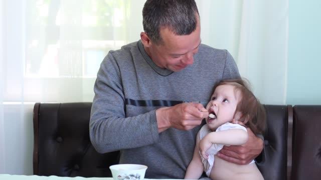 Un padre ama de casa. El niño es travieso. Un hombre alimenta a hija con cucharas - vídeo