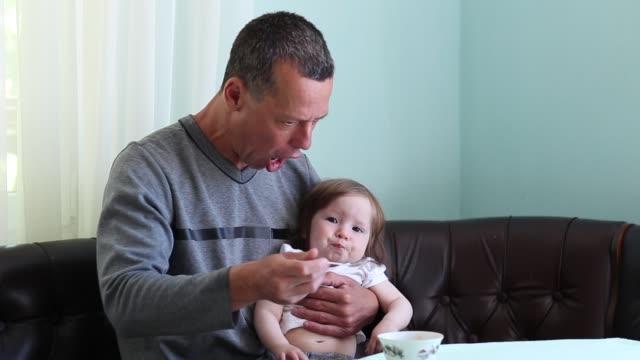 Ein Hausmann. Das Baby ist frech. Ein Mann füttert Tochter mit Löffel – Video