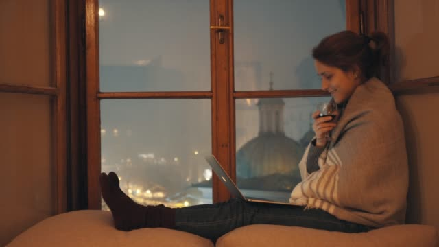 Staying home during COVID-19 pandemic Woman at home sitting near the window, enjoying movie on laptop and drinking red wine stay home stock videos & royalty-free footage