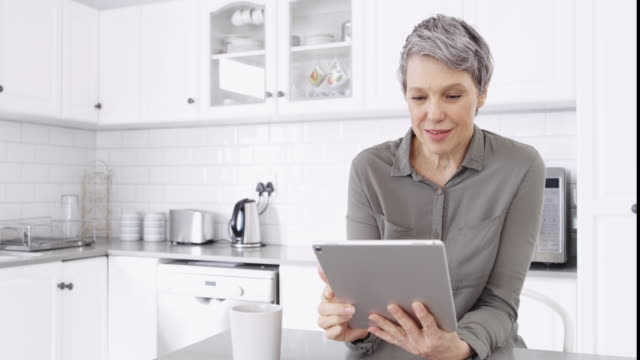 Staying informed with what's happening out there 4k video footage of a mature woman using a digital tablet at home short hair stock videos & royalty-free footage
