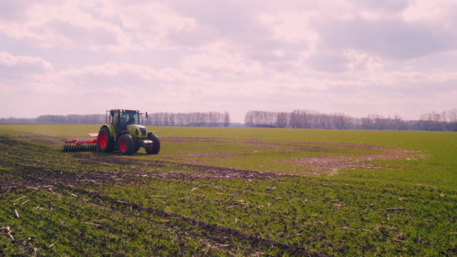 Steadicam fly around shot: The tractor plows the land in the field early in the spring on a clear sunny day video