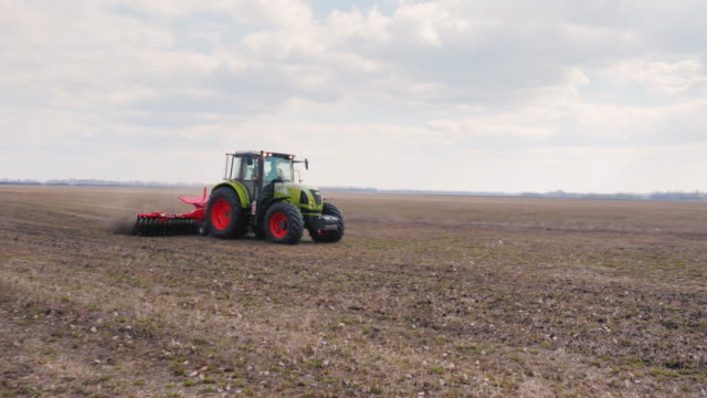 Steadicam fly around shot: The tractor plows the land on the field. Agribusiness is modern video