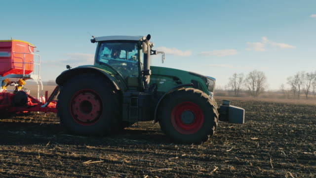 Steadicam pan shot: A tractor with a large seeder is driving across the field in the sun video