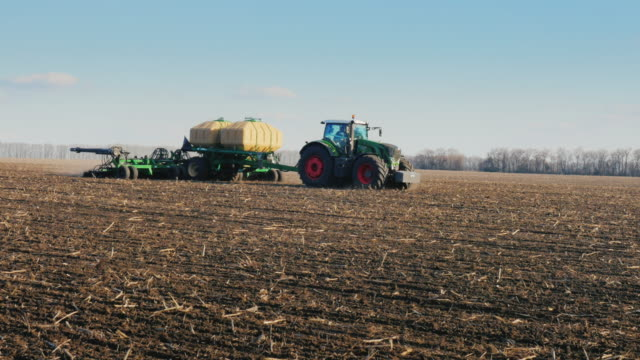 Steadicam pan shot: tractors with seeders sow wheat on the field in early spring. Side view video