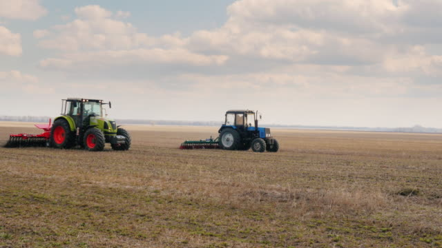 Steadicam pan shot: Two tractors go ahead on the field, cultivate the ground video