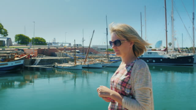 Steadicam shot: A female tourist walks along the docks with yachts. Barcelona, Spain