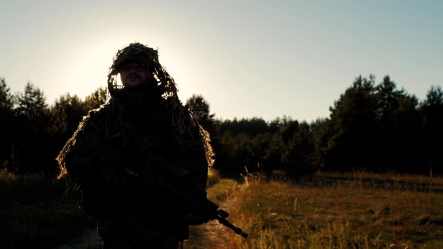 Steadicam shot: Armed with a man walking on a country road at sunset video
