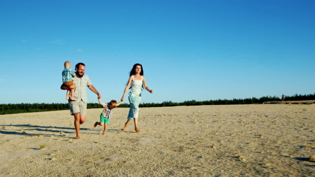 Steadicam shot: Cheerful family running across the sand. Parents and two young sons video