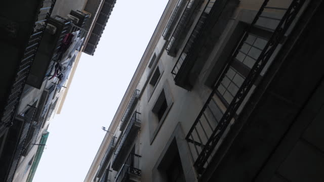 Steadicam shot: house with balconies in Barcelona's Gothic Quarter. Facades of old houses in the narrow streets of Barcelona. Traveling concept. Slow motion video