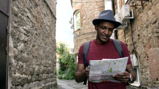 Steadicam shot of African american tourist man walking and watching paper city map to find directions to famous place video