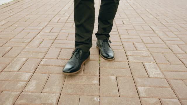 vidéos et rushes de steadicam coup de closeup découvre un homme d'affaires en chaussures de marche avant trottoir à la rue - mode bureau