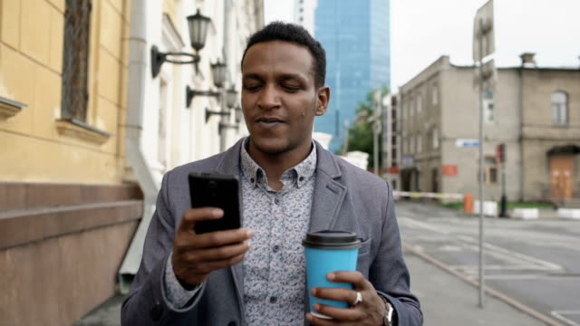 Steadicam coup de jeune entrepreneur heureux à l'aide de smartphone et marchant avec une tasse de café en plein air - Vidéo