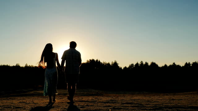 Steadicam shot: Silhouette of a young couple, which goes towards the setting sun. Back view video