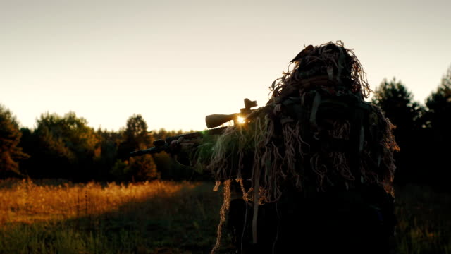 Steadicam shot: Sniper in a camouflage outfit moved cautiously, looks through the scope of weapons. At sunset video