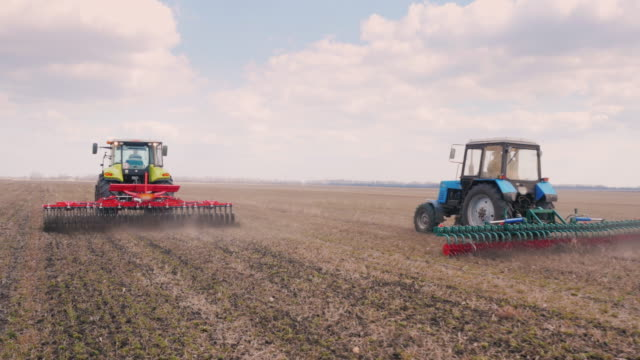 Steadicam shot: Two tractors go ahead on the field, cultivate the ground video