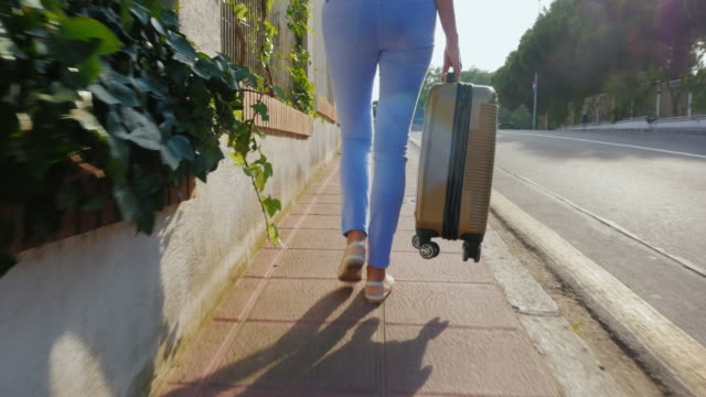 steadicam shot: woman tourist walking on the road with a travel bag. spain resort. back view - donna valigia solitudine video stock e b–roll