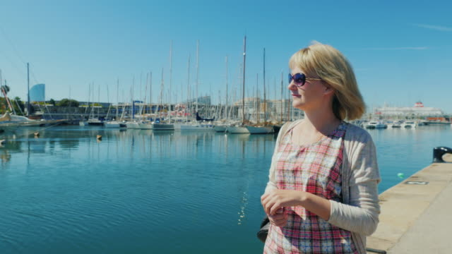 Steadicam shot: Young woman in sunglasses walking on the quay with yachts. Barcelona, Spain