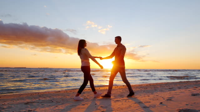 Steadicam slow motion shot: Romantic couple walking on the beach at sunset, holding hands, having a good time Romantic couple walking on the beach at sunset, holding hands, having a good time. ProRes HQ 10 bit video young couple stock videos & royalty-free footage