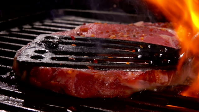 Steak is pressed by kitchen spatula to the grill Tasty pork steak flipping on the grill. Steak is pressed by kitchen spatula to the grill seared stock videos & royalty-free footage