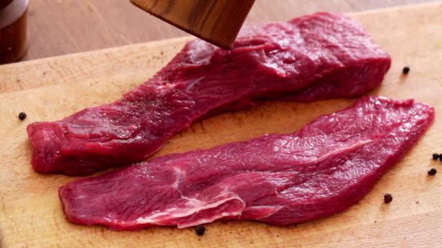 Steak seasoning HD 1080 STATIC: Steak slices being seasoned with pepper using pepper mill;  jerky stock videos & royalty-free footage