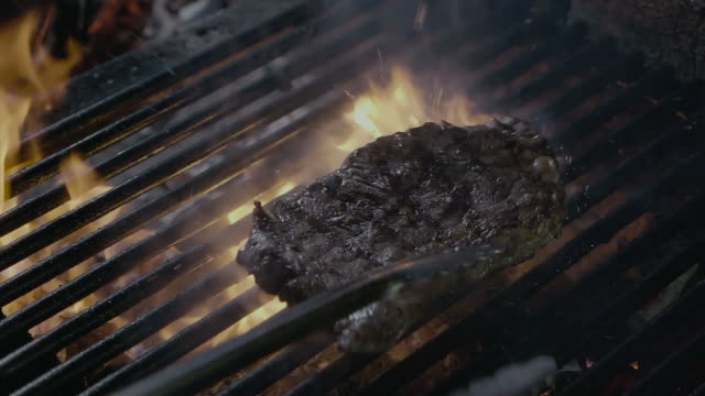 steak slipping on the grill with fire slow mo - szpatułka przybór do gotowania filmów i materiałów b-roll