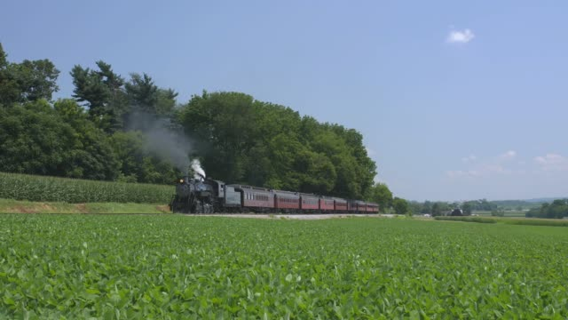 A 1924 Steam Engine with Passenger Train Puffing Smoke Traveling Along the Amish Countryside