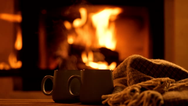 Steam from a cups with a hot cocoa on the fireplace background. video