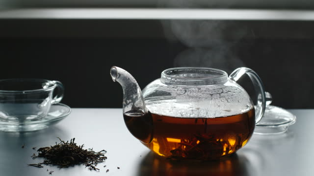 Steam from a teapot on a table. Near is tea crop and glass cup
