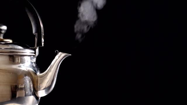 dampf aus kochendem teekanne auf schwarzem hintergrund - gar gekocht stock-videos und b-roll-filmmaterial