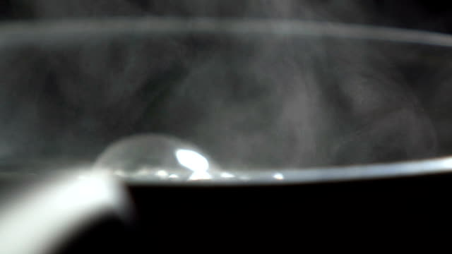 Steam from Boiling water in coating pan heating on electronic stove video
