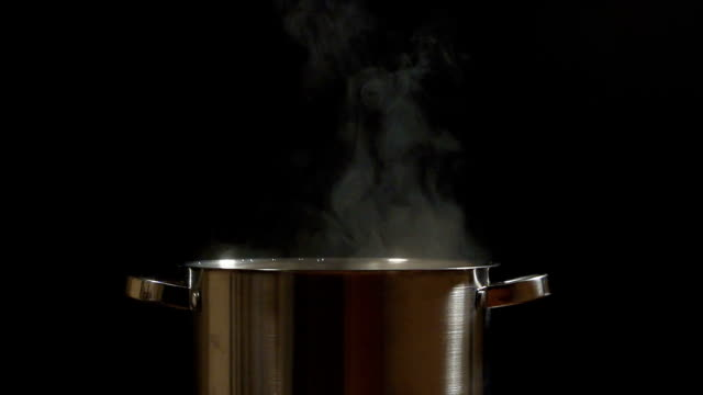 SLOW: Steam lifts up over a steel pan SLOW: A steam lifts up over a steel pan on a black background cooking pan stock videos & royalty-free footage