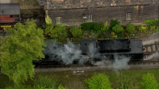 steam locomotive leaving oakworth station - Aerial View - England,  Bradford,  United Kingdom video
