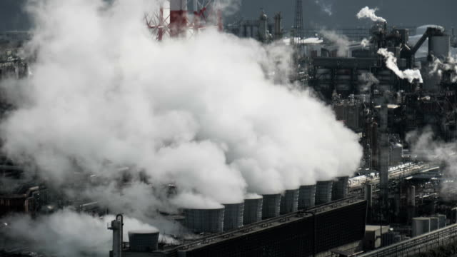 Steam or smoke from pipes in factory at industry area